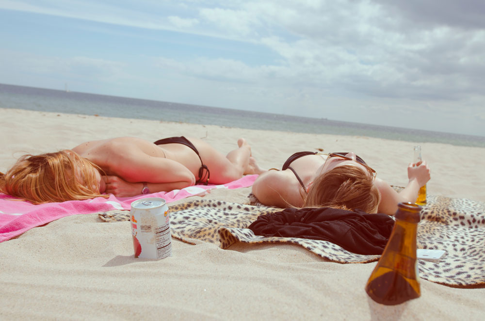 Two girls laying on the beach tanning